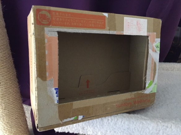 """To complete the project, I cut a hole into a Suntory shipping box from Japan that is the exact same size as the 7"""" Touchscreen Display box, which would work well, too. It is works well for holding up the Raspberry Pi and storing its accessories when I go between home and work."""