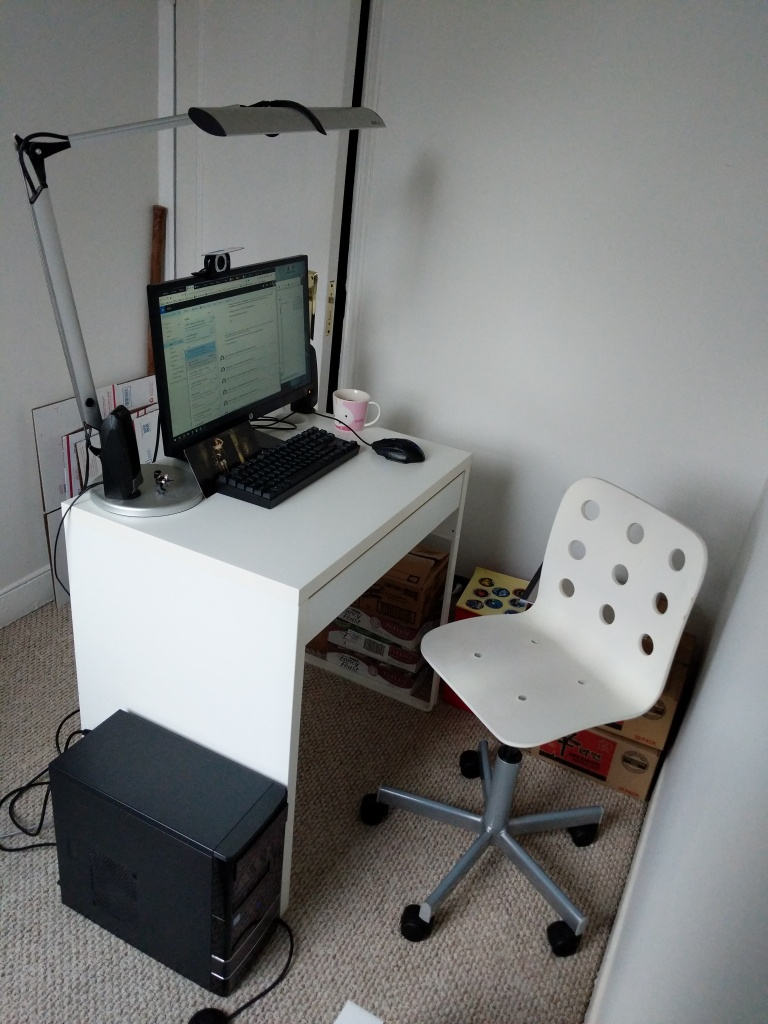 Computer desk with monitor, webcam, lamp, and chair. The desk is 2 feet away from the wall.